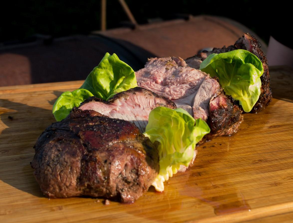 Een gesneden stuk vlees op een plank, aangekleed met stukjes sla