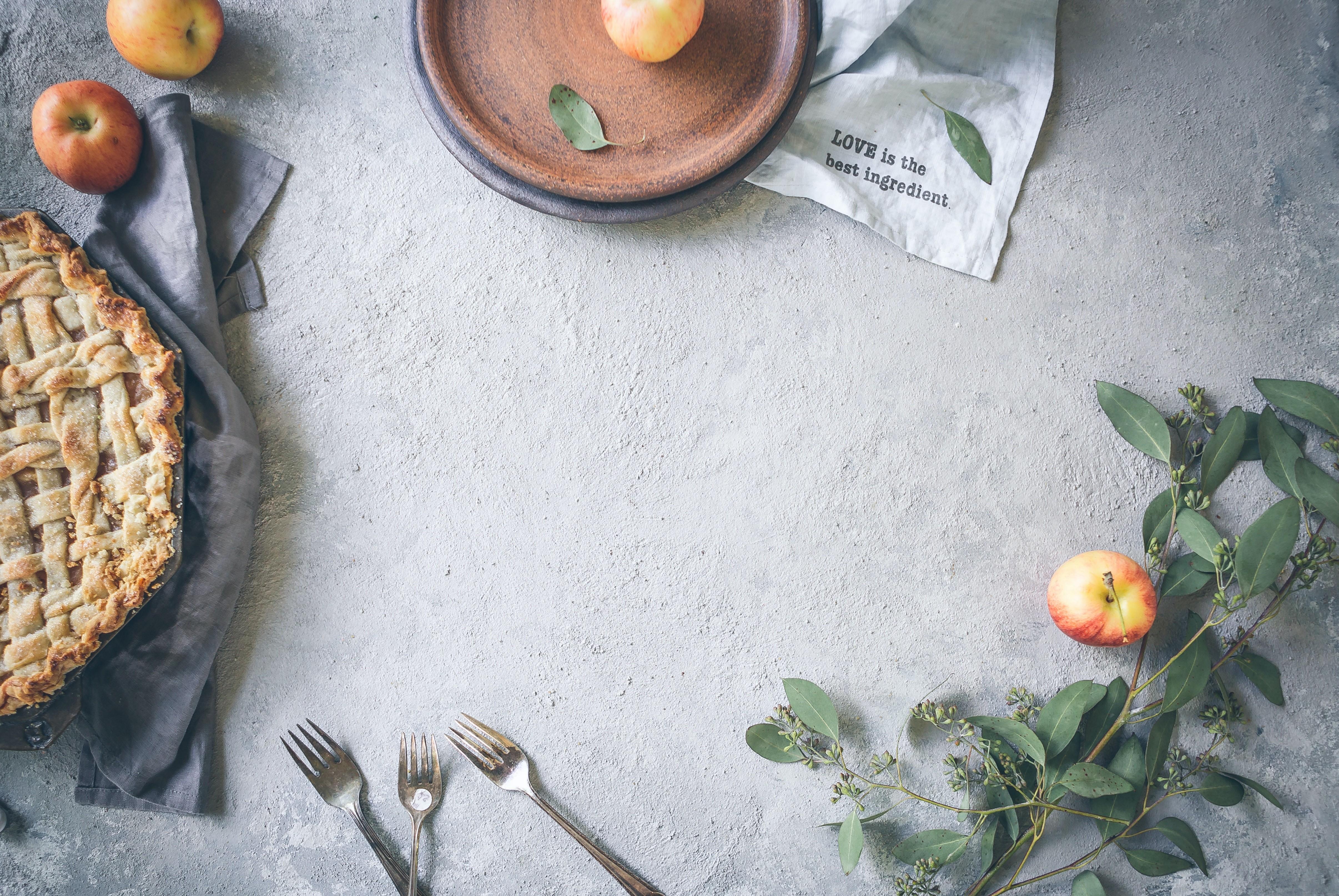Een appeltaart op een tafelkleed met aankleding.